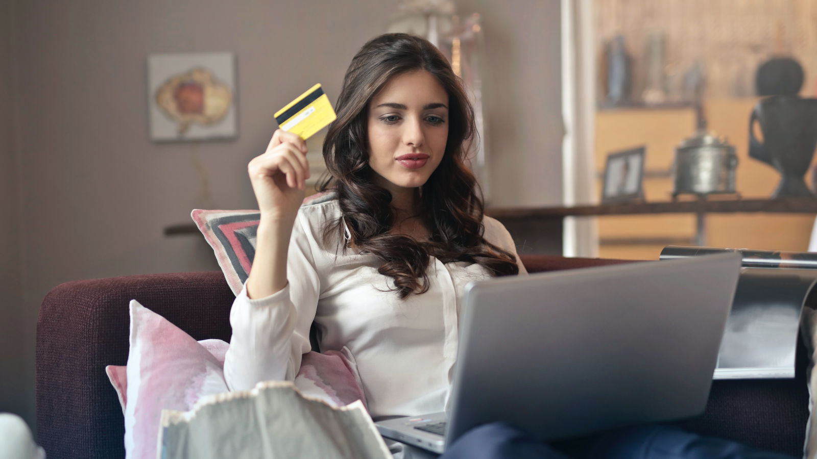 Onlineshopperin mit Laptop und Kreditkarte